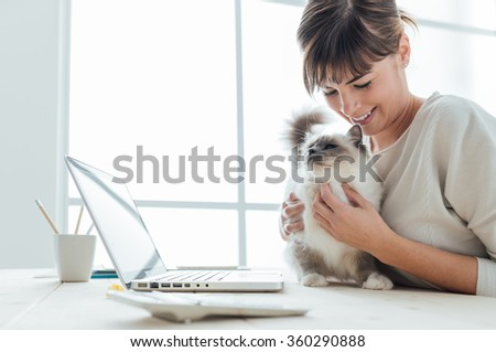Young woman sitting at desk and cuddling her lovely cat, togetherness and pets concept - stock photo