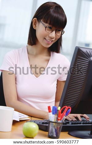 Young woman sitting at desk, looking at computer