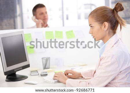 Young woman sitting at desk, working on computer, busy.? - stock photo