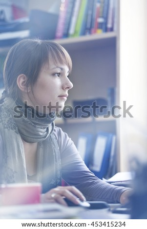 Young woman sitting at her office desk while she is working very concentrated with the computer