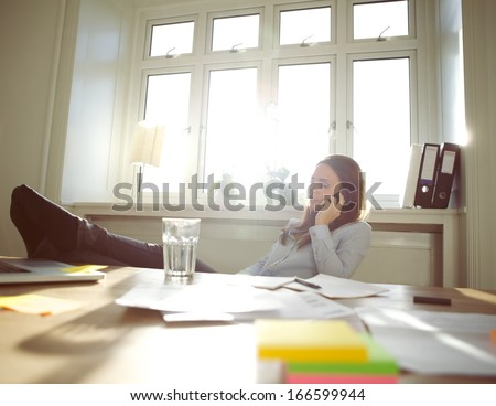 Young woman sitting at her table with legs on desk talking on mobile phone. Caucasian businesswoman using cell phone while relaxing at her desk. Female working from home office. - stock photo