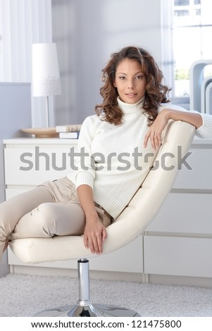 Young woman sitting at home in design chair.