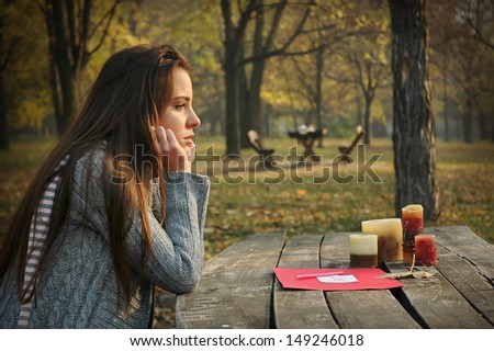 young woman sitting at old wooden table with paper and candles on it, in autumn park, pensive look - stock photo