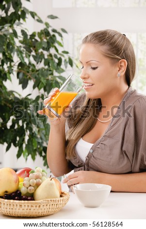 Young woman sitting at table having breakfast, drinking orange juice.