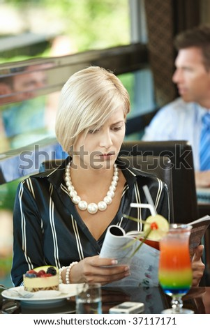 Young woman sitting at table in cafe, reading magazine.