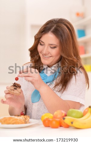 Young woman sitting at table with fruits and cake. Dieting concept