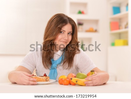 Young woman sitting at table with fruits and cake. Dieting concept - stock photo