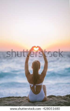 Young woman sitting at the beach and holding hands in heart shape