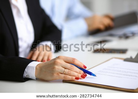 Young woman sitting  at the desk with folder .