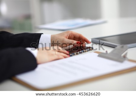 Young woman sitting at the desk with folder . - stock photo