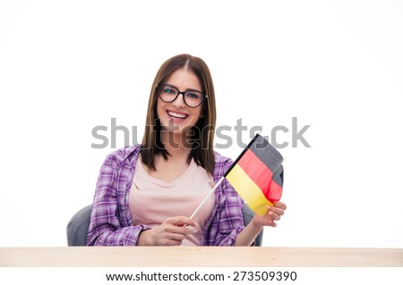 Young woman sitting at the table with German flag over white background and looking at camera - stock photo