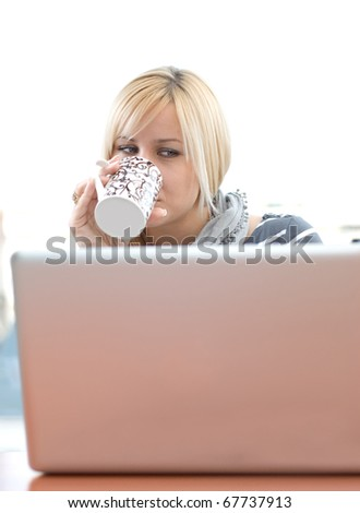 young woman sitting at the table with laptop and drinks coffee