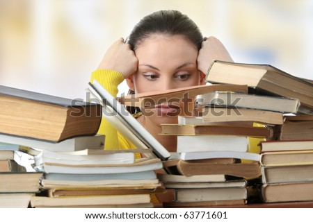 Young woman sitting behind books - stock photo