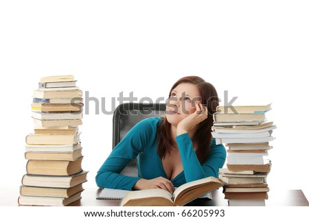Young woman sitting behind books and dreaming, isolated on white