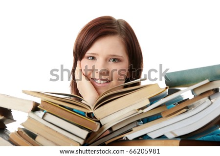 Young woman sitting behind books, isolated on white