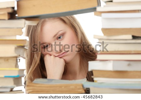 Young woman sitting behind books - tired - stock photo