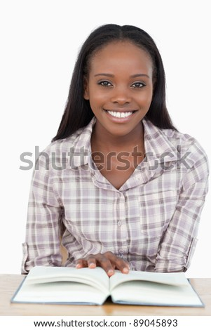 Young woman sitting behind the table reading a book against a white background