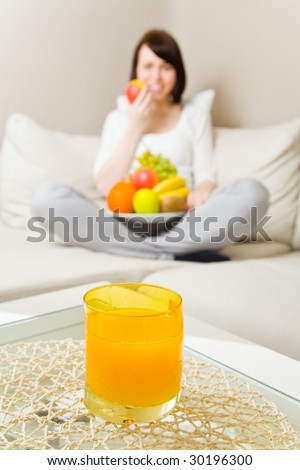 Young woman sitting cross-legged and eating fruits with orange juice on a table - stock photo