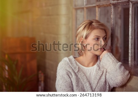 Young woman sitting daydreaming or waiting for someone staring out of a window in the living room with a serious expression - stock photo