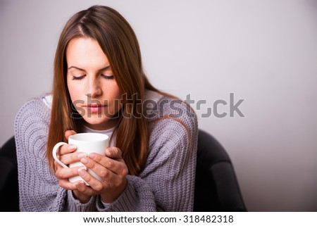 Young woman sitting in a chair drinking a hot cup of maybe tea, coffee, hot chocolate or soup. gently blowing on the contents of the mug. - stock photo