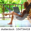 Young woman sitting in a hammock in garden with laptop - stock photo