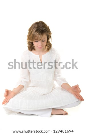 Young woman sitting in a meditative pose on a white background