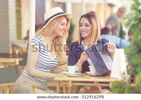 Young woman sitting in a sidewalk cafe and showing to her friend what did she buy - stock photo