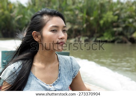 Young woman sitting in a taxi boat on canal - way to the monastery Wat Khun Samut - stock photo