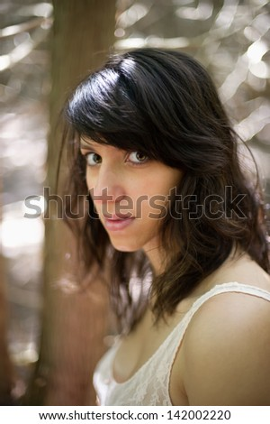 young woman sitting in a wooded area facing the camera in a head and shoulders portriate pose with selective focus