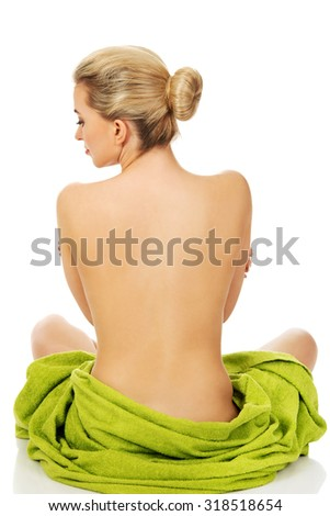 Young woman sitting in a yoga position covered with green towel