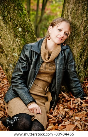 Young woman sitting in autumn leaves and leaning against a tree