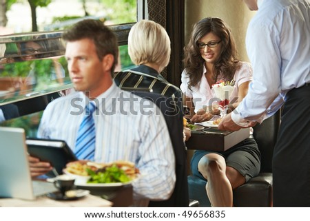 Young woman sitting in cafe, waiter serving sweets. Businessman eating club sandwich and working in the forground. Selective focus on women. - stock photo