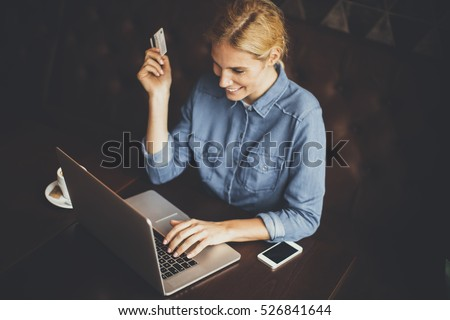 Young woman sitting in cafeteria and perform online shopping