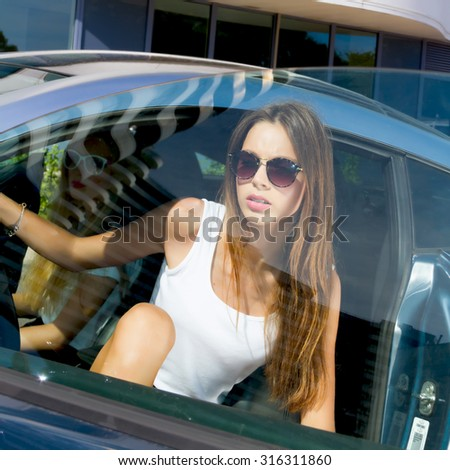 Young woman sitting in car.Portrait of Young teenage brunette student girl sitting driver seat in luxury blue sport car.Slim cute brunette woman inside black leather chair auto open door and going out - stock photo