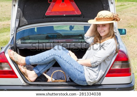 young woman sitting in car trunk outdoor - stock photo