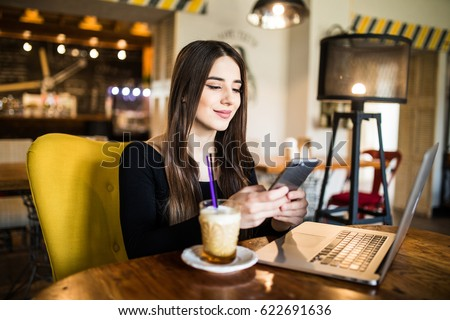 stock photo young woman sitting in coffee shop at wooden table drinking coffee and using smartphone female 622691636 How Does the bitcoin Era Application Work?