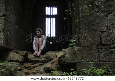 Young woman sitting in dungeon of old castle in Brittany