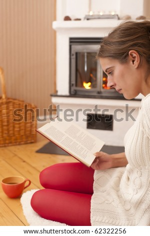 Young woman sitting in front of a fireplace, reading a book. Warm colors, looks like at home during a winter day. - stock photo