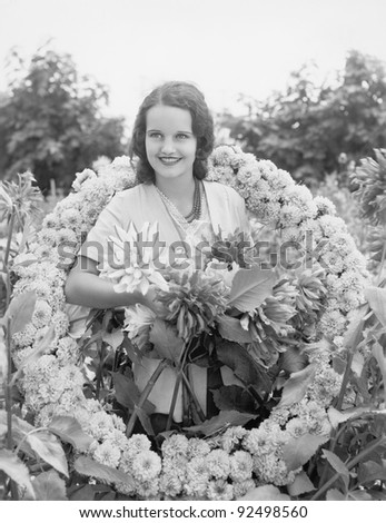 Young woman sitting in garden in a wreath of flowers - stock photo