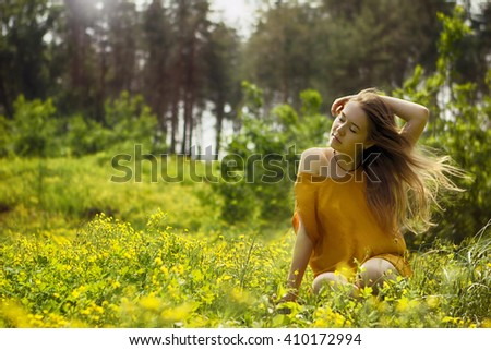 Young woman sitting in grass with flowers