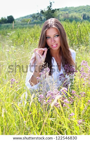 Young woman sitting in green grass - stock photo