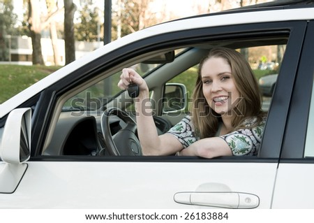young woman sitting in her car holding and showing off her car keys, very happy