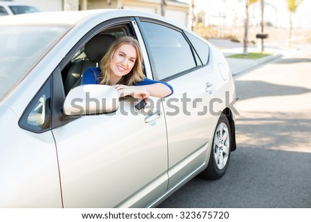 Young woman sitting in her car holding keys - stock photo