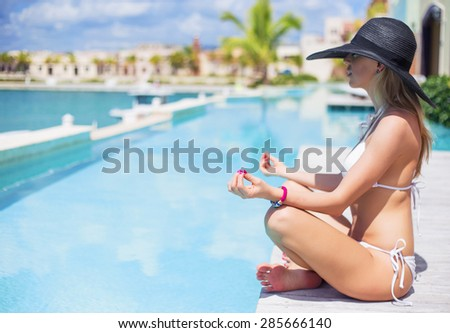 Young woman sitting in lotus pose by the pool