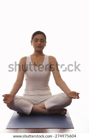 Young woman sitting in lotus position on mat