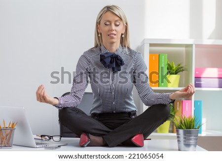 Young woman sitting in lotus yoga pose on desk in office - stock photo
