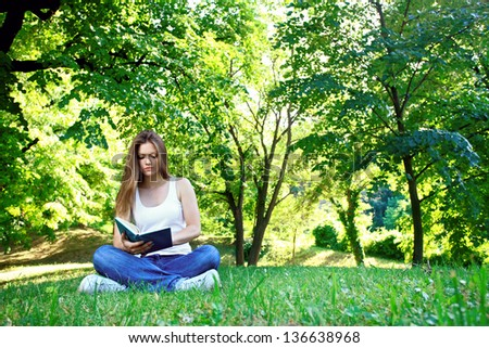 Young woman sitting in park and reading book - stock photo