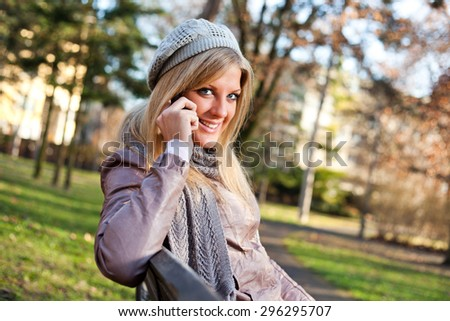 Young woman sitting in park and talking on mobile phone