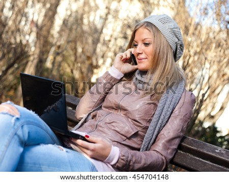 Young woman sitting in park, using laptop and talking on mobile phone - stock photo