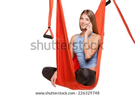 Young woman sitting in red hammock for anti-gravity aerial yoga with phone on a white background.